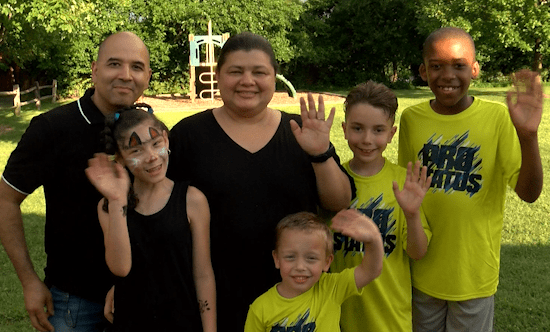 The Daniels foster family waves happily at picnic