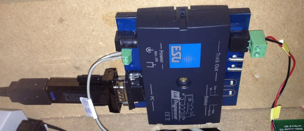 """The ESU Lokprogrammer installed next to my command station. Power provided by a standard 16V model railroad power supply. The Serial to USB adapter is a """"Digitus"""" FTDI-based adapter bought separately to replace the failing original cable."""