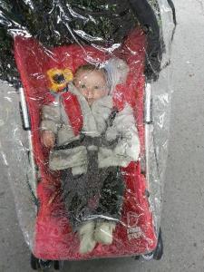 Iris en su sillita con la burbuja para la lluvia en Praga