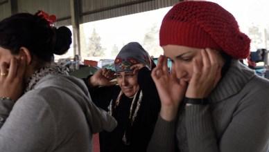 Syrische vluchtelingen in Idomeni (aan de grens met Macedonië) stoppen hun oren af voor overvliegende jets van de Griekse luchtmacht. Deze geluiden kennen ze al.