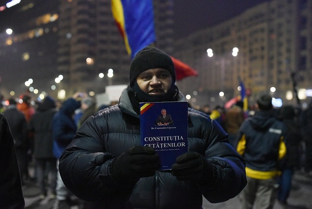 Tijdens een protestactie aan het ministerie van justitie op 31 januari 2017 houdt deze betoger een exemplaar van de Roemeense Grondwet voor zich
