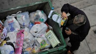 Een Griekse bedelaar verzamelt restjes uit blikken olijfolie in de vuilnisbakken om ze terug te verkopen