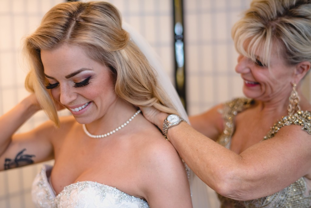 bride and mother putting on necklace