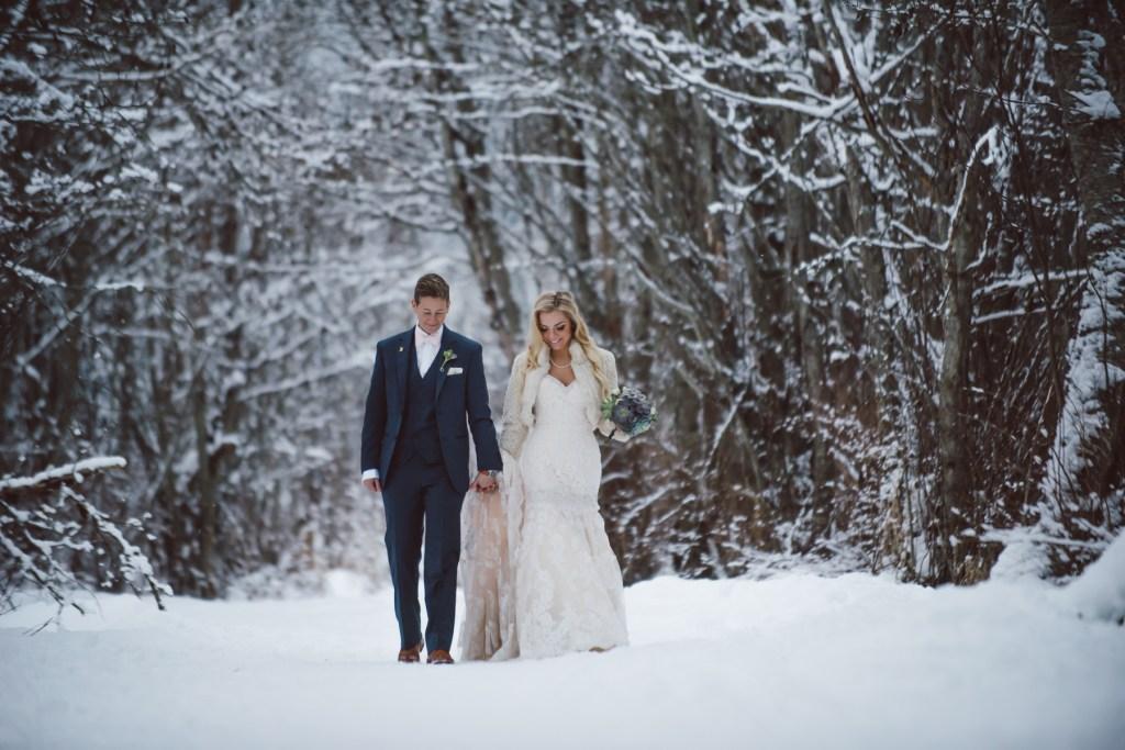A beautiful wedding couple walk through the snowy woods on their wedding day