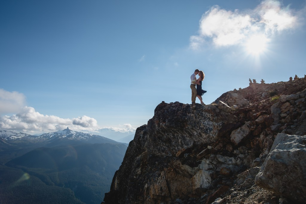 A couple hugging on Whistler peak with black tusk in the distance