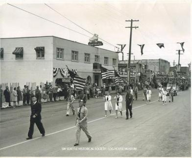 Parade in White Center, Vern Gould leading the procession down 16th Ave SW. Some of the businesses visible are the Southgate Roller Rink, Sherrill's Ice Cream, J&W Tavern, and the A&B Tavern. August 1947 SWSHS 2005.001.0665