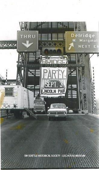 """The locked open West Seattle bridge span with the celebration party banner clearly visible in 1984. Neighborhoods within West Seattle were greatly impacted when the bridge was hit by a freighter in 1978. It took six years to get the funds and build the current """"high bridge"""". (Photo by Chris Styron. SWSHS/Log House Museum 2005.32.343"""