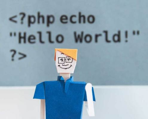 Paperdoll man with glasses in front of a snippet of Hello World code