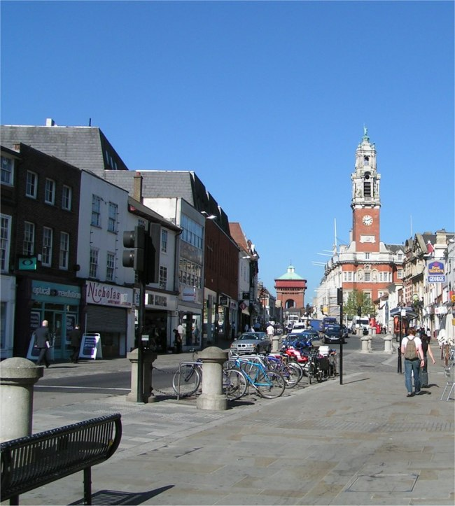 Weekend trips from London to historic towns, high street with clocktower and shops in Colchester
