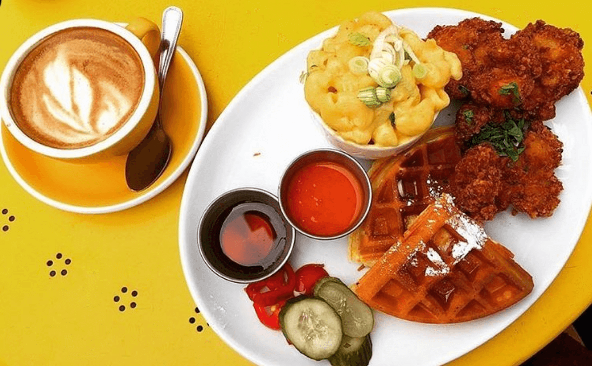 Chicken and waffle with mac & cheese and a coffee on yellow table at breakfast Club in London