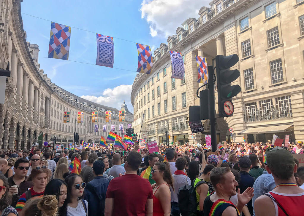 Regent street with lots of people and rainbow flags during pride celebrations in London