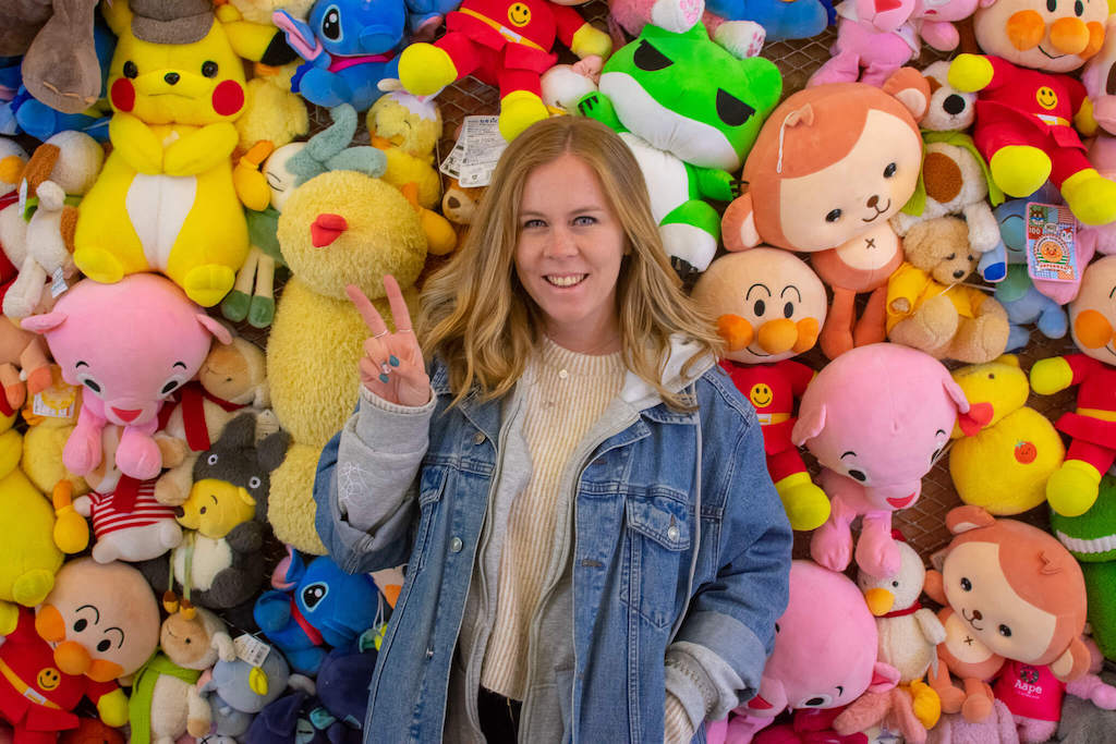 Girl in front of wall of childrens toys in China