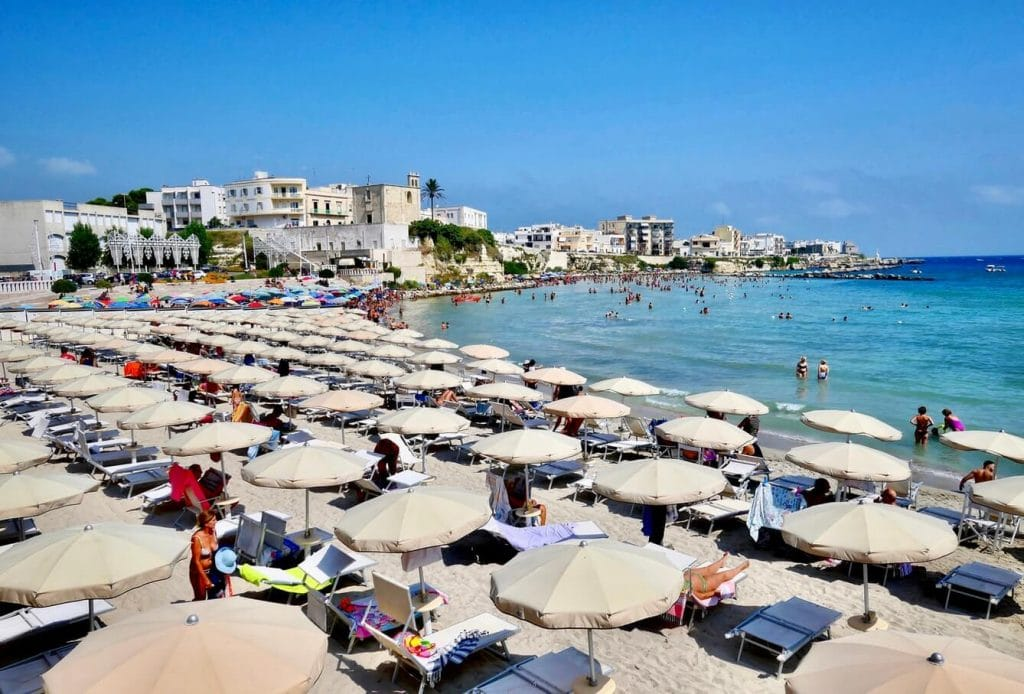 Busy Otranto beach with sunbeds in Puglia