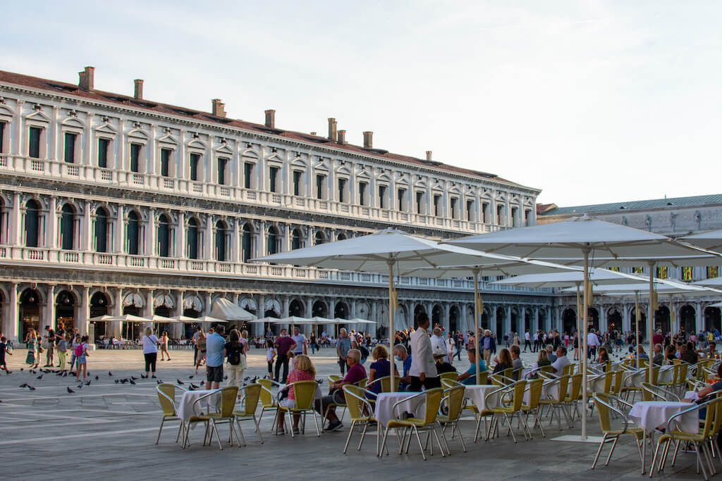 St Marks Square with tables outside cafes in Venice Italy