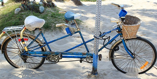 Picture taken on Venice Beach in LA of a blue tandem bike in the sand
