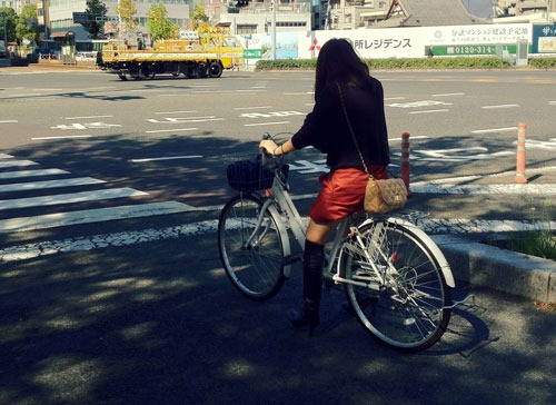 Cyclist waiting at a traffic light in Japan