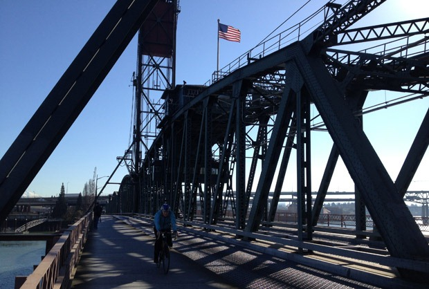 A cyclist passes over a bridge in Portland
