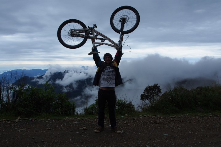 Andreas holding up bike at the edge of the Bolivian death road