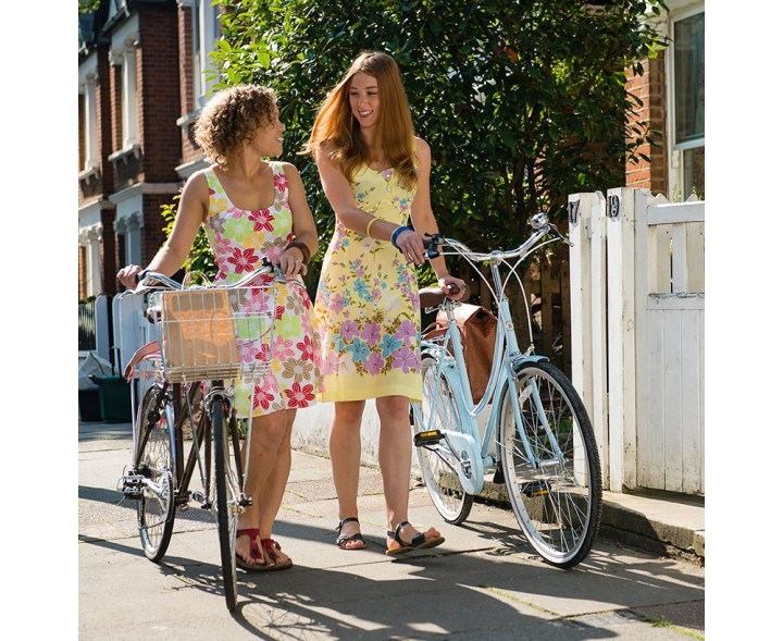 Picture of two young women walking with their bikes