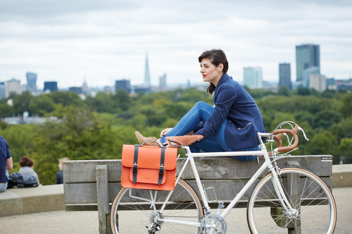 Photograph of woman sitting on bench with Hills & Ellis orange bike bag