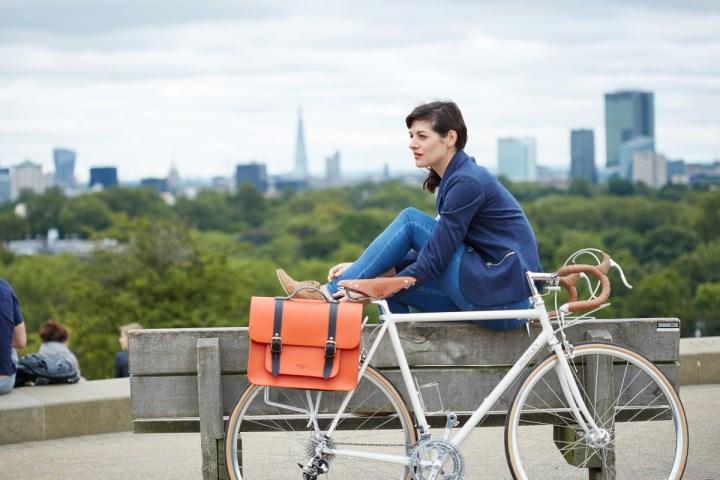 Photograph of woman sitting on bench with Hills & Ellis orange bike bag