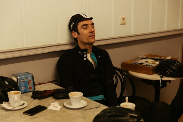 Photograph of man in cafe wearing Rapha Pro Team Cycling Cap