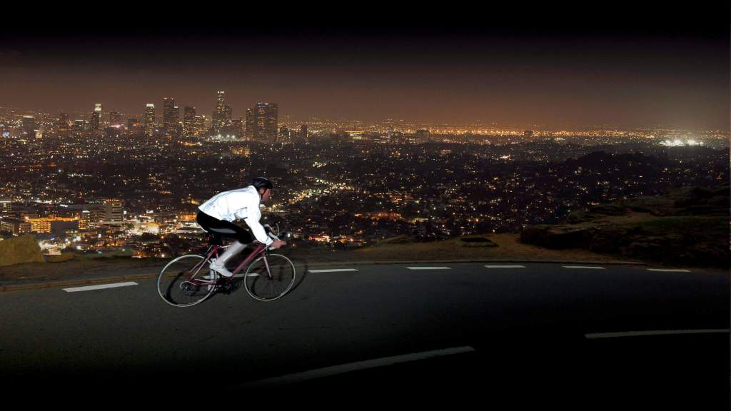 Cyclist in Proviz 360+ jacket cycling at night above cityscape
