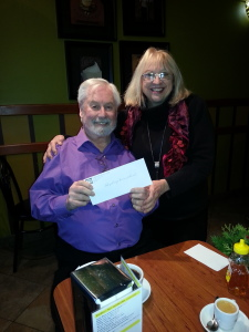 Ernie is presented with a cheque from LPM Treasurer Jenny for $5000.