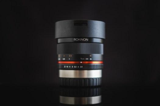 The Rokinon 8mm f/2.8 UMC Fisheye II has a built in petal hood and a cylindrical lens cap.