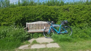 Bike in front of a wooden bench.