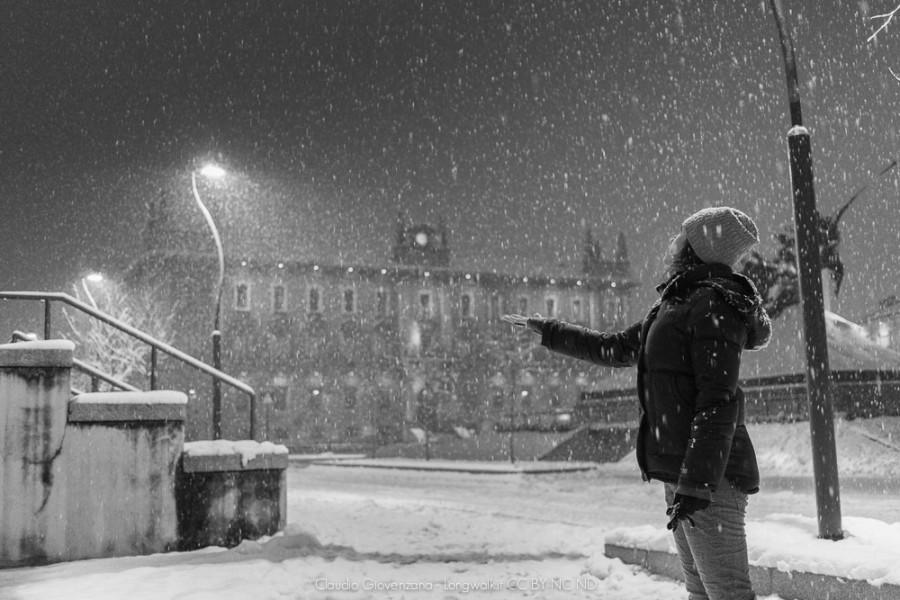 una ragazza sotto una splendida nevicata urbana