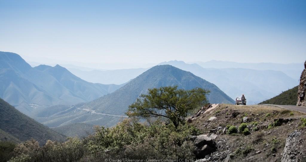 Un uomo cammina su una strada del Messico Orientale tra panorami infiniti e il ripetersi delle montagne della sierra