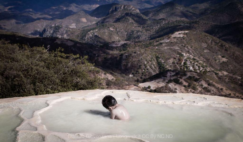 Un bambino solo nelle acque del Messico di fronte a una valle