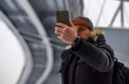 man in gray jacket holding iPhone 11 Pro Max