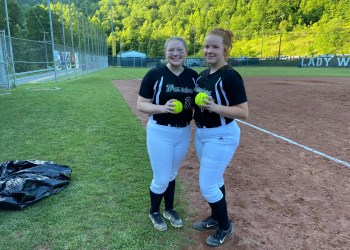 Wyoming East's Andrea Laxton (left) and Megan Cook (right) pose with their home run balls after beating Independence 5-2 Tuesday night in New Richmond.