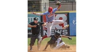 Independence shortstop Michael McKinney  jumps above North Marion runner Bryce Rhoades who slides in safely with a double during Class AA State Tournament action in Charleston. (F. Brian Ferguson/Lootpress)