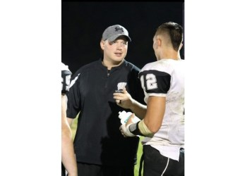 Westside head coach Tyler Dunigon (left) talks with a player during a game last season in Clear Fork. (Photo Credit: Jim Cook)