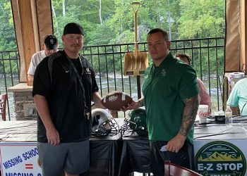 Westside head coach Tyler Dunigon (left) and Wyoming East head coach Jimmy Adkins (right) pose for a picture at the conclusion of the E-Z Stop Stores event in Pineville on Tuesday.
