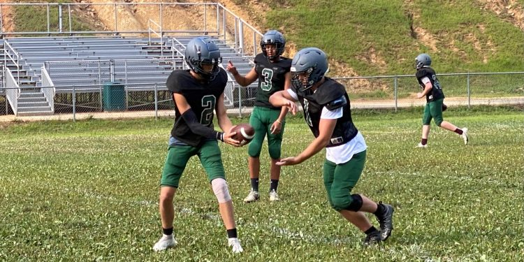 Wyoming East quarterback Jackson Danielson practices a handoff in New Richmond on Tuesday evening.