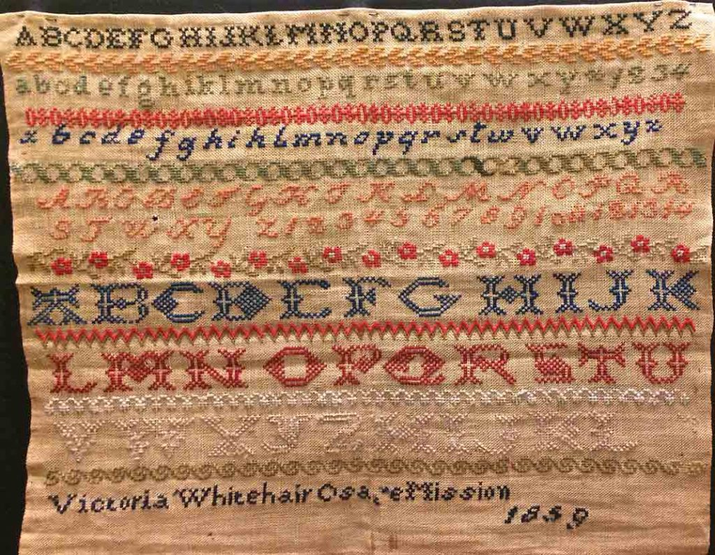 1859 needlework sampler by Victoria Whitehair, age 12, a student at the Osage Mission in Kansas.