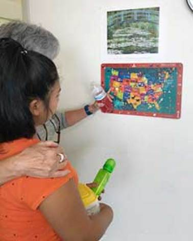 A volunteer points out California on a map of the United States. (Photo courtesy of Vivian Doremus)