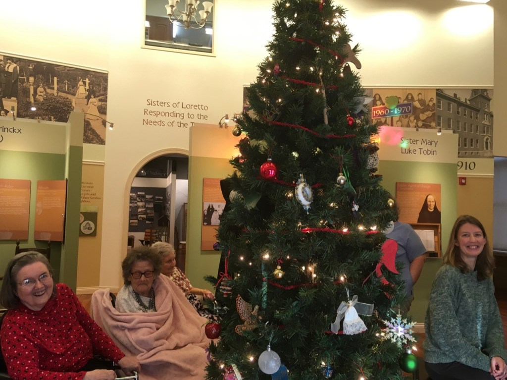 Residents of the Motherhouse Infirmary and Loretto staff around a Christmas tree in the Heritage Center