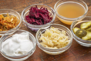 Bowls of fermented foods to strengthen your gut microbiome and fight depression: kimchee, sauerkraust, yogurt