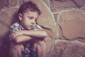 Child sits alone listless, depressed.