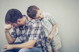 Little boy hugs his depressed dad. Does depression run families?