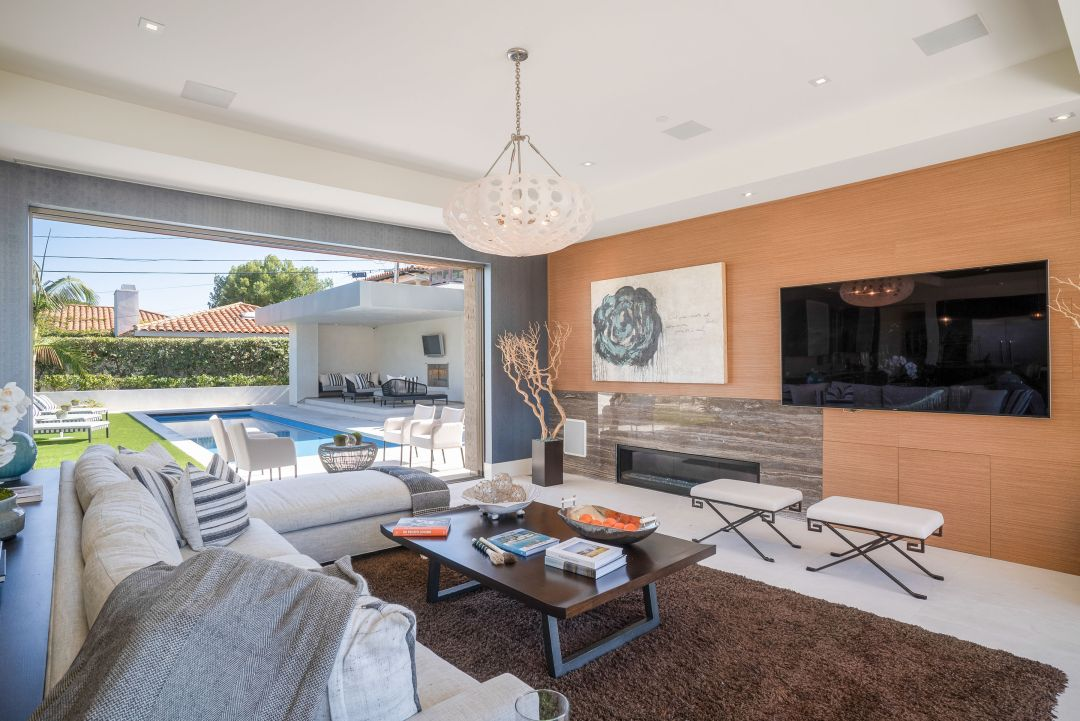 Manhattan Beach Living Room features full wall sliding window system for indoor outdoor feel, organic shape lighting fixtures, and luxury architectural details