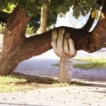 A wooden hand holding up the think branch of a tree leaning to the right.