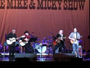 Mike Nesmith and Micky Dolenz in concert, flnaked by lead guitarist left and Christian Nesmith right.