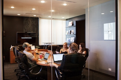 Several employees sitting around a wooden conference table, behind glass doors, discussing something.