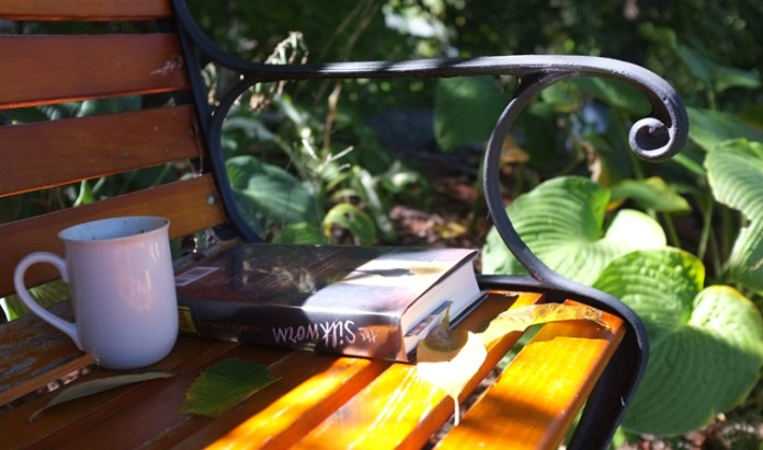 coffee and book on a bench